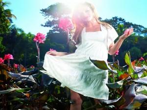 Postal: Una joven en verano entre bellas flores