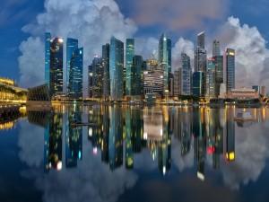 Edificios iluminados en Singapur se reflejan en el agua