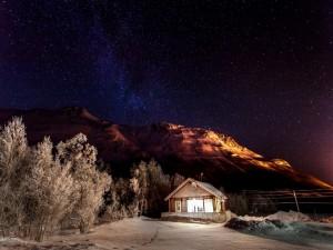 Casa en la nieve bajo el cielo cubierto de estrellas