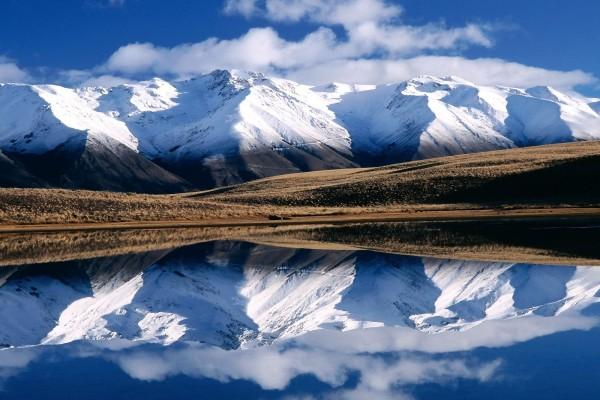 Montañas y cielo reflejados en el agua