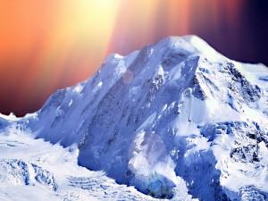 Rayos del sol caen sobre una montaña cubierta de nieve