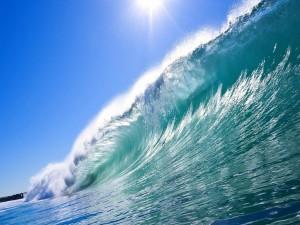 El sol iluminando la cresta de la ola