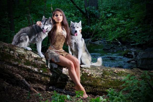 Hermosa mujer con dos perros junto a un río