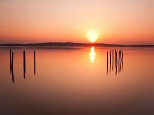 Postal: Resplandecientes rayos de sol se reflejan en el lago