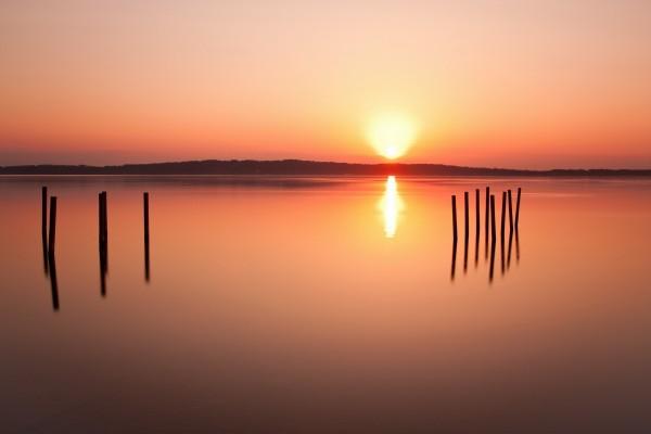 Resplandecientes rayos de sol se reflejan en el lago