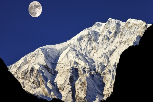 Resplandeciente Luna iluminando los picos montañosos cubiertos de nieve