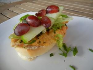 Rebanada de pan con pollo, manzana y uvas