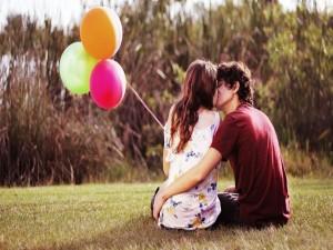 Pareja de enamorados besándose sobre la hierba