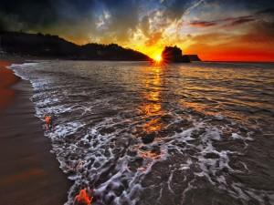 Postal: Una playa iluminada por el sol al atardecer