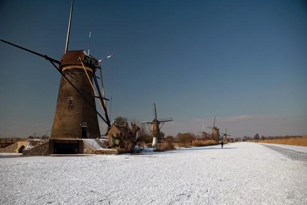 Molinos de viento junto a un canal cubierto de hielo