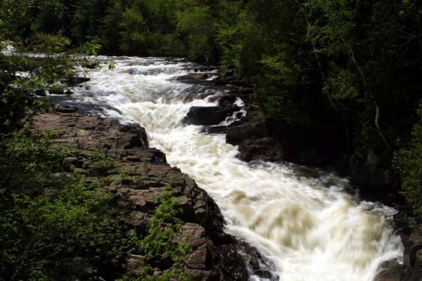 Un caudaloso río entre rocas y árboles