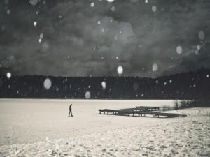 Un hombre solitario caminando bajo la nieve