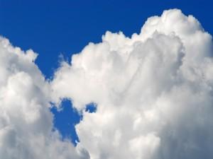 Postal: Densas nubes blancas en un cielo azul