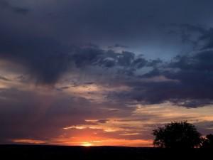 Postal: Últimos rayos de sol iluminando el cielo