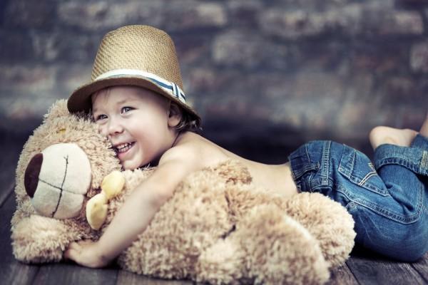 Sonriente bebé abrazado a un oso de peluche