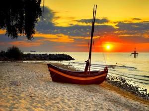 Postal: Barca sobre la arena de la playa en el ocaso del sol