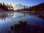 Bruma sobre el lago y en la montaña al amanecer