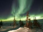 Aurora boreal iluminando el paisaje nevado