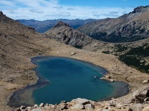 Postal: Lago azul entre rocas polvorientas