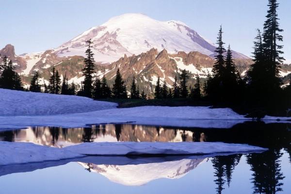Montaña nevada reflejada en el agua helada