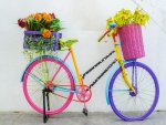 Bicicleta de colores con canastas de flores