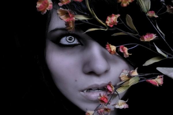 Vampiresa tras unas flores