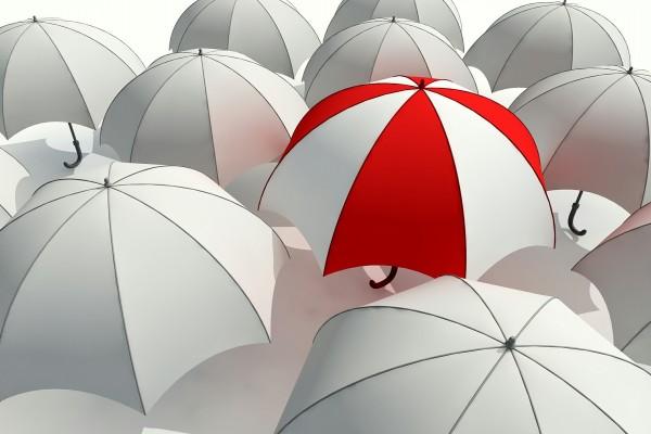Paraguas rojo y blanco entre varios paraguas blancos