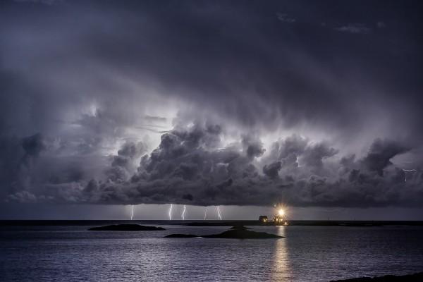 Faro iluminando en una noche de tormenta eléctrica