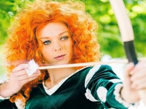 Una actriz pelirroja con un arco y flecha