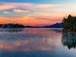 Cielo al amanecer y árboles reflejados en las tranquilas aguas del lago