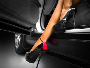 Mujer con zapatos de tacón saliendo del coche