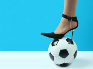 Postal: Zapato de tacón sobre un balón de fútbol