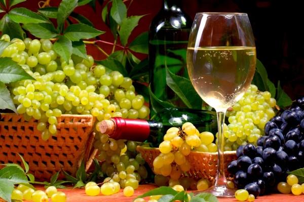 Una copa con vino blanco y uvas sobre la mesa