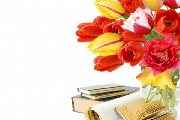 Libros junto a un jarrón con tulipanes