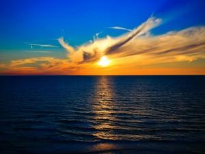 Postal: Puesta de sol en el horizonte iluminando las aguas del océano
