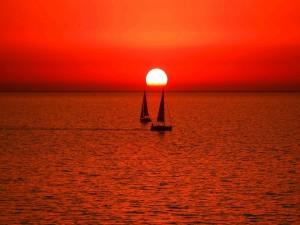 El sol se esconde, iluminando los barcos a vela
