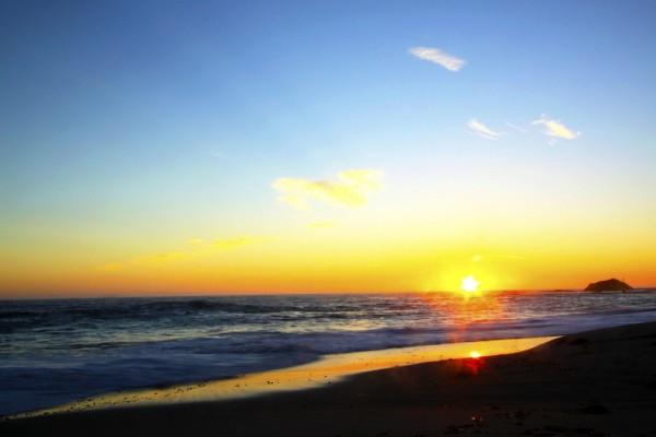 El sol del atardecer reflejado en la orilla del mar