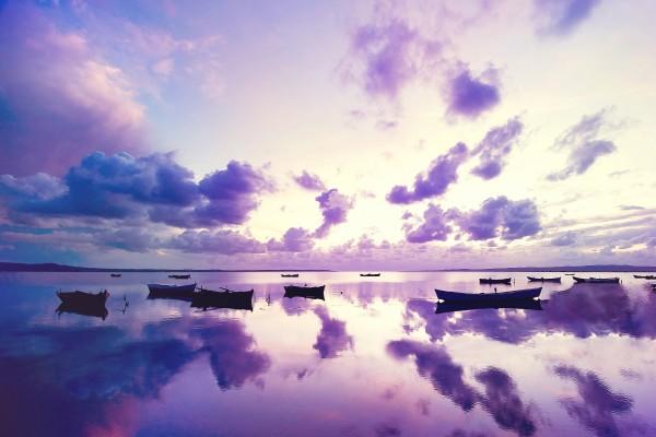 Nubes y barcas reflejadas en el mar
