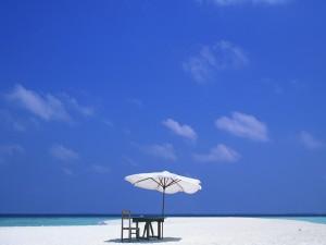 Postal: Mesa y silla de madera bajo una sombrilla blanca en la playa