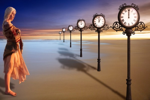 Una mujer junto a varios relojes que marcan diferentes minutos