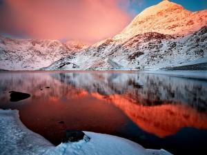 Postal: Montañas nevadas se reflejan en las aguas del lago