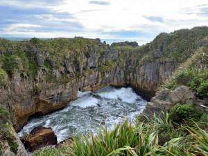 Postal: Las olas chocan contra las rocas erosionándolas del acantilado