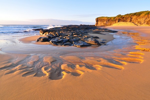 El agua se va retirando de la playa dejando sus huellas