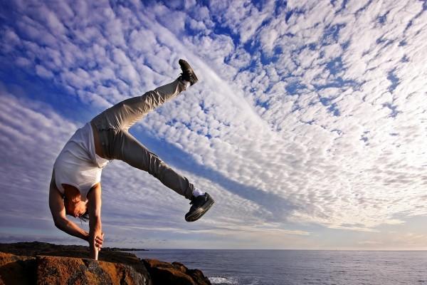 Hombre realizando ejercicios de equilibrio junto al mar