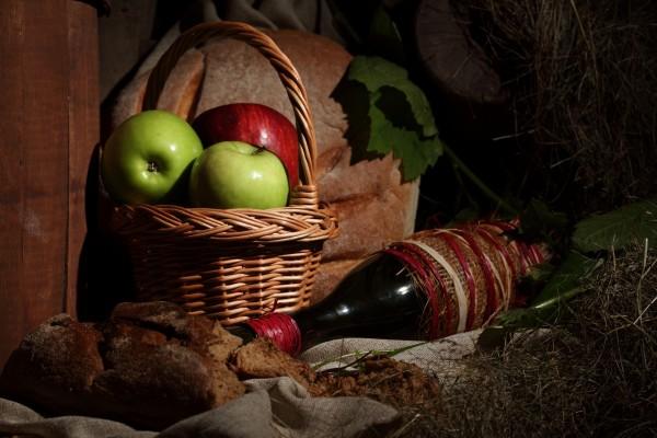 Botella de vino, pan y manzanas