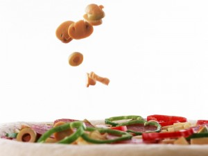 Champiñones y aceitunas cayendo sobre una pizza sin hornear