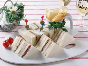 Bandeja blanca con sándwiches y dos copas de vino blanco