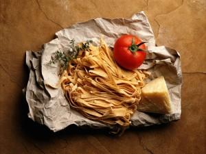 Postal: Tallarines frescos, queso y un tomate sobre el mismo papel