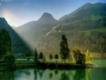 Rayos de sol iluminando los árboles y el lago