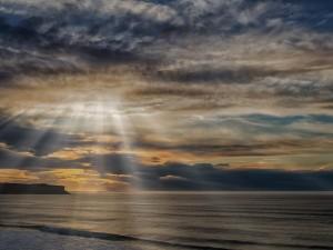 Los rayos del sol atraviesan las nubes iluminando las aguas del mar